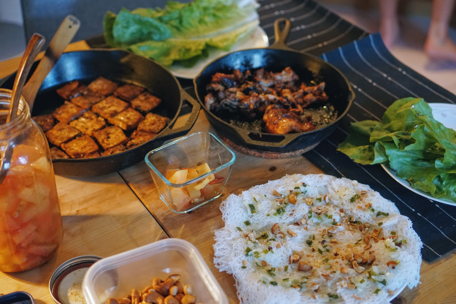 Multiple plates on a table including vermicelli, grilled chicken and tofu