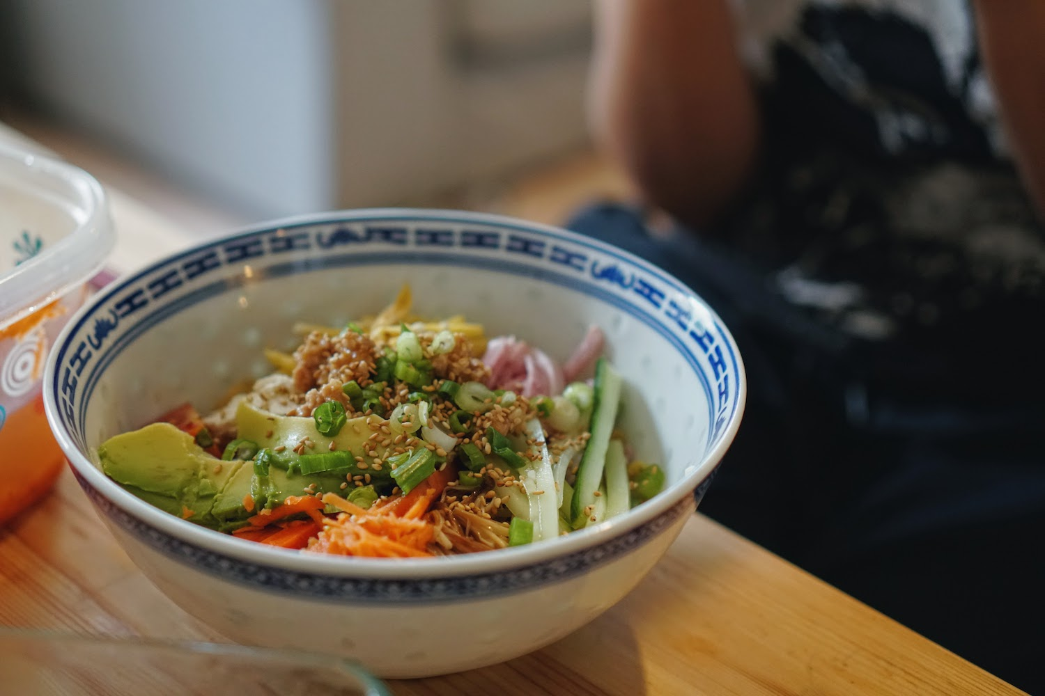 A bowl of noodles topped with avocado, carrot, scallion