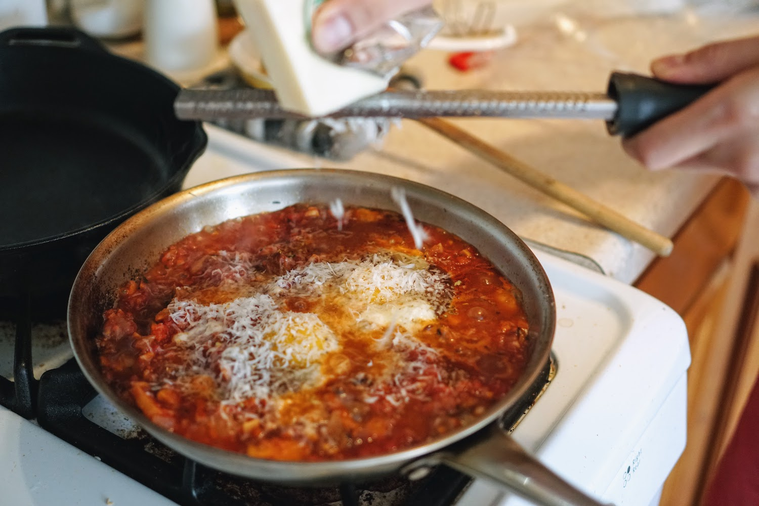 Grating parmesan cheese on top of eggs in tomato sauce