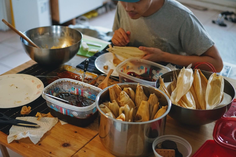 Kevin at a table assembling tamales